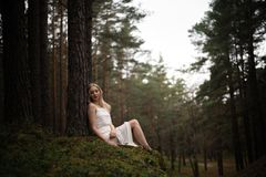 Beautiful young blonde woman sitting in forest nymph in white dress in evergreen wood stock photos