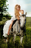 Young blonde bride riding a horse in fashionable dress. Beautiful young blonde woman sitting on a horse in white dress, in green garden Stock Photos