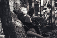Beautiful young blonde woman sitting near the hay in the yard in rural areas. black-white Stock Images