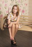 Beautiful young blonde woman sitting in a trendy shoes and white dress Stock Photo