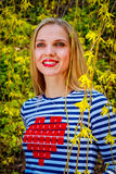 Beautiful young blonde woman is smiling in a blooming garden. Beautiful young blonde woman in blooming garden Royalty Free Stock Images