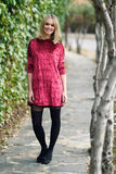 Beautiful young blonde woman smiling in urban background. Beautiful blonde woman smiling in urban background. Young girl wearing red dress and tights standing in Royalty Free Stock Photography
