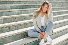 Beautiful young blonde woman smiling on urban steps. Beautiful young caucasian woman smiling in urban background. Blond girl wearing casual clothes in the Stock Photos