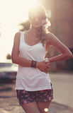 Beautiful young blonde woman standing on the beach. Wearing white T-shirt. Wind is blowing into her long blonde hair. In Royalty Free Stock Photos