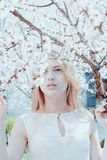 Beautiful young blonde woman. Standing near the apple tree Stock Photo