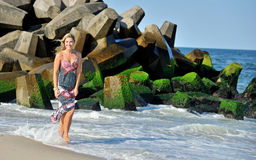 Beautiful young blonde woman in sundress on beach Stock Photos