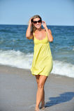 Beautiful young blonde woman in sundress on beach Stock Photo