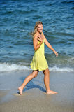 Beautiful young blonde woman in sundress on beach Stock Image
