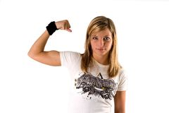 Beautiful young blonde woman in a tee shirt making a muscle. Portrait of a beautiful young blonde woman in a tee shirt making a muscle isolated on a white Stock Image