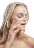 Beautiful young blonde woman touching her smooth skin Royalty Free Stock Photos