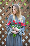 Beautiful young blonde woman with tulips bouquet on against the background of a wooden fence Royalty Free Stock Photography