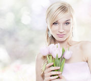 Beautiful young blonde woman with tulips bouquet. On spring delicate background royalty free stock photography