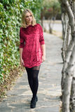 Beautiful young blonde woman in urban background. Beautiful blonde woman in urban background. Young girl wearing red dress and tights standing in the street royalty free stock image