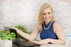 Beautiful young blonde woman using laptop Royalty Free Stock Photo