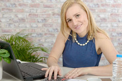 Beautiful young blonde woman using laptop Royalty Free Stock Images