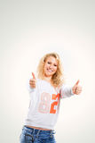 Beautiful young blonde woman in a vest and jeans on  white background with arms outstretched  the thumbs up. Beautiful young blonde woman in a vest and jeans on Royalty Free Stock Photos