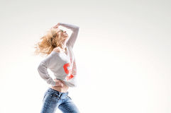 Beautiful young blonde woman in a vest and jeans on  white background with energetic dance moves. Beautiful young blonde woman in a vest and jeans on a white Stock Photography