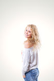 Beautiful young blonde woman in a vest and jeans on a white background. Portrait of a beautiful young blonde woman in a vest and jeans on a white background Stock Photos