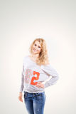 Beautiful young blonde woman in a vest and jeans on  white background. Beautiful young blonde woman in a vest and jeans on a white background, put a hand on her Stock Photos