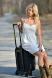 Beautiful young blonde woman waiting with suitcase Stock Photo