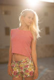 Beautiful young blonde woman on a walk arownd the city near to the castle in summer sunny day stock photography