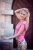 Beautiful young blonde woman on a walk arownd the city near to the castle in summer sunny day Royalty Free Stock Photo