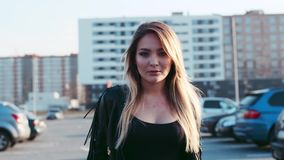 Beautiful young blonde woman walking down the parking in a bright sunlight, looks to camera and smiles seductively. Hot stock video