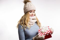 Beautiful young blonde woman in warm clothes with gift box on hand on white background. Happy girl wearing beige knitted hat, stock image