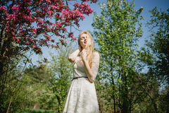 Beautiful young blonde woman in white dress walking at spring park near pink cherry trees. She enjoys nature with closed Royalty Free Stock Photos