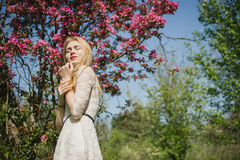 Beautiful young blonde woman in white dress walking at spring park near pink cherry trees. She enjoys nature with closed Royalty Free Stock Photo