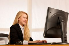 Beautiful young blonde woman working on computer in her office Royalty Free Stock Photos