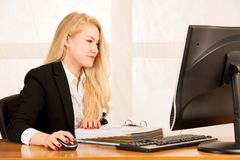 Beautiful young blonde woman working on computer in her office Stock Photos