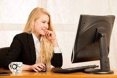 Beautiful young blonde woman working on computer in her office.  stock photos