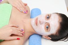 Beautiful young blue eye woman with clay facial mask Stock Photo