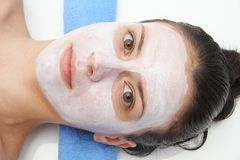 Beautiful young blue eye woman with clay facial mask Royalty Free Stock Photos