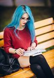 Beautiful young blue-haired grunge rock girl sitting on bench in square and reading book Stock Image