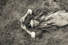 Beautiful young boho girl in jacket lying down on grass royalty free stock photos