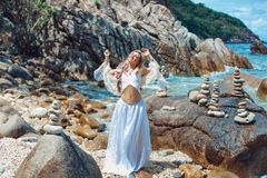 Beautiful young boho style woman in white dress on stone beach Royalty Free Stock Photography