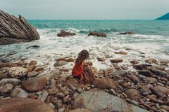 Beautiful young boho styled woman sitting on a stone beach. And looking on a horizon line Stock Photography