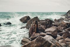 Beautiful young boho styled woman sitting on a stone beach. Waves and splash Stock Image