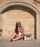 Beautiful young boho woman with a retro stereo sitting on a stre Royalty Free Stock Image