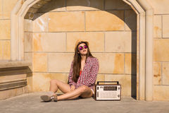 Beautiful young boho woman with a retro stereo sitting on a stre Stock Photography