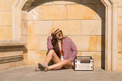 Beautiful young boho woman with a retro stereo sitting on a stre Stock Images