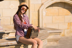 Beautiful young boho woman with a retro stereo sitting on a stre Royalty Free Stock Photography