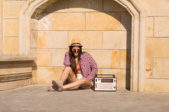 Beautiful young boho woman with a retro stereo sitting on a stre Royalty Free Stock Photo