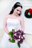 Beautiful Young Bride. A beautiful young bride holding a bouquet of purple and white flowers Royalty Free Stock Photo