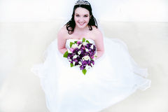 Beautiful Young Bride. A beautiful young bride holding a bouquet of purple and white flowers Stock Image
