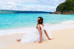 Beautiful young bride with angel wings on the sea coast. Tropical sea in the background. Beautiful young bride with angel wings on the sea coast. Tropical sea stock photography