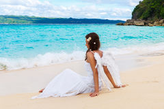 Beautiful young bride with angel wings on the sea coast. Tropical sea in the background. Beautiful young bride with angel wings on the sea coast. Tropical sea stock image