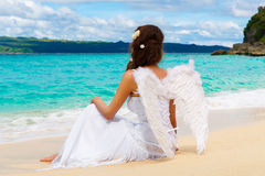 Beautiful young bride with angel wings on the sea coast. Tropical sea in the background. Beautiful young bride with angel wings on the sea coast. Tropical sea stock photo